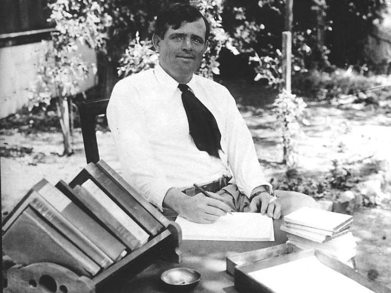Jack London writing outside.